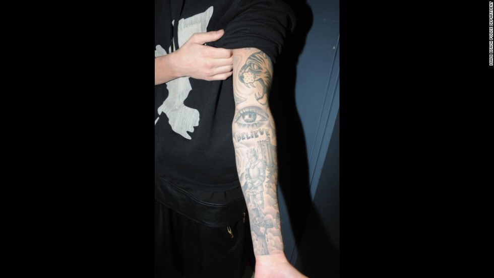 "One of Bieber's arms is sleeved with multiple tattoos including a tiger head, an eye, the word ""believe"" and a knight with a castle."