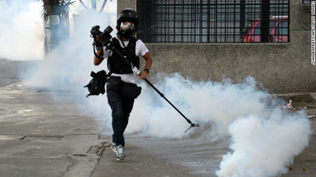 Cameraman runs away from tear gas during an anti-government protest in Caracas on February 22, 2014. Hundreds of thousands of Venezuelans took to the streets of Caracas in marches for and against President Nicolas Maduro's government Saturday, as the nation's massive divide became ever more evident. The protests -- which began on February 4 -- are seen as the biggest test yet to socialist leader Maduro since he succeeded late leftist icon Hugo Chavez last year, with the country's economic problems at the heart of often bloody marches that have left 10 people dead and scores injured. AFP PHOTO/ JUAN BARRETO (Photo credit should read JUAN BARRETO/AFP/Getty Images)