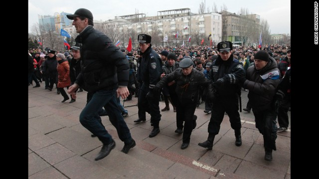 Demonstrators waving Russian flags break a police barrier as they storm a regional administrative building in Donetsk, Ukraine, on Wednesday, March 5.