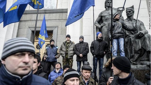 Men carrying far-right Svoboda flags wait in front of the Ukrainian Parliament in Kiev on February 27.