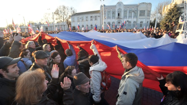Pro-Russian activists carry a huge Russian flag during their rally in the western Crimean city of Yevpatoria on March 5, 2014.