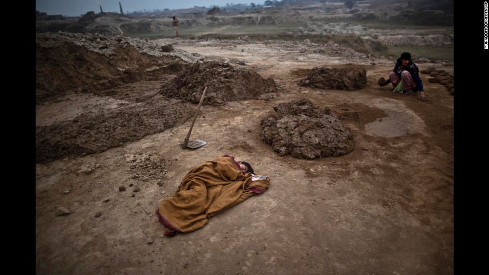 Adil Shahid, a 6-year-old boy suffering from a fever, sleeps on the ground close to his mother, Najma, at the brick factory where she works near Rawalpindi, Pakistan, on Monday, March 3.