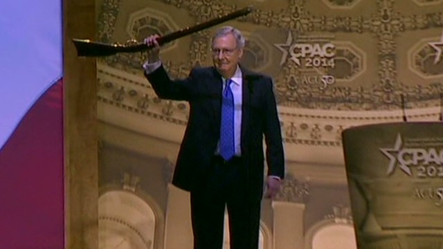 Mitch McConnell waves a rifle at CPAC