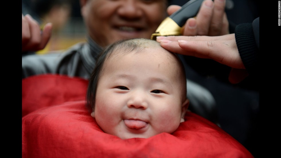 "A baby has his hair cut in Hefei, China, on Sunday, March 2. Many in China believe it is good luck to have your hair cut on the second day of the second lunar month, known in Chinese as Er Yue Er, or ""a time for the dragon to raise its head."""