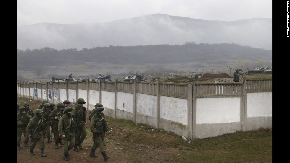 Armed men believed to be Russian military march in a village outside Simferopol on Friday, March 7.