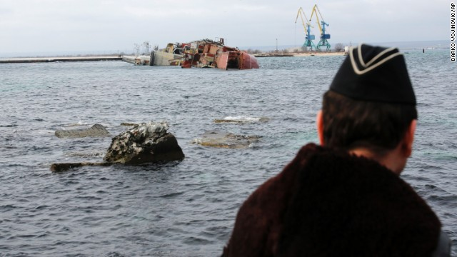 A Ukrainian Navy officer looks at the scuttled, decommissioned Russian vessel Ochakov from the Black Sea shore outside the town of Myrnyi, Ukraine, on Thursday, March 6. In the early hours of the day, Russian naval personnel scuttled the decommissioned ship, blockading access for five Ukrainian Naval vessels now trapped inside of the Southern Naval Headquarters.