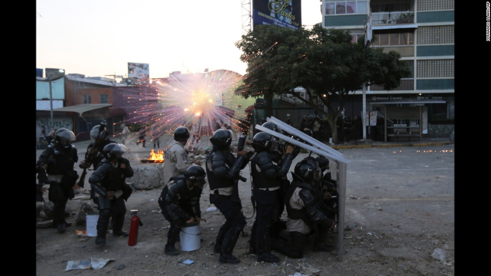 National Guard members take cover as a firecracker launched by protesters explodes nearby in Caracas on Wednesday, March 5.