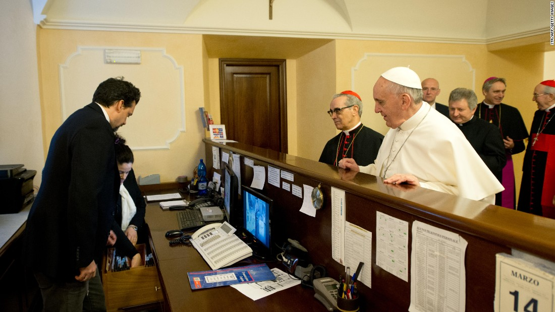Francis stands at the reception desk of the Domus Internationalis Paulus VI residence on March 14, 2013, where he paid the bill for his stay during the conclave that would elect him leader of the world's 1.2 billion Catholics.