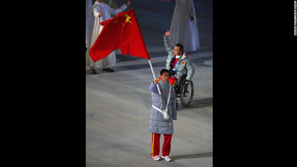 Chinese skier Ye Tian holds his country's flag.