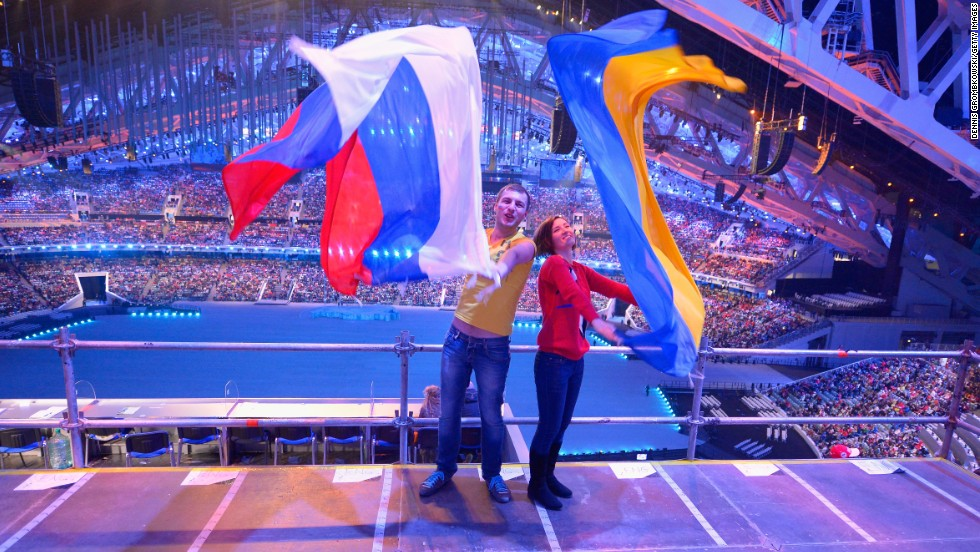 Two spectators pose with Russian and Ukrainian flags during the ceremony.