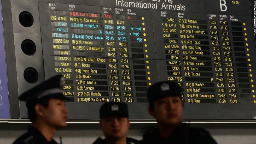 Policía chinos junto al tablero que muestra la información en rojo del vuelo MH370 en el aeropuerto de Beijing el 8 de marzo.