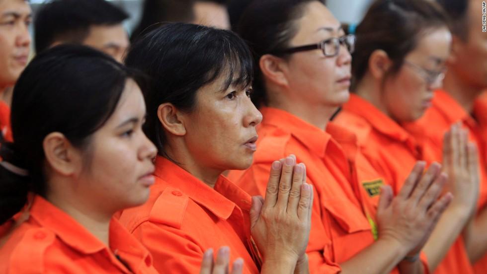 Los miembros del equipo de rescate de Fo Guang Shan oran el domingo 9 de marzo, en el aeropuerto internacional de Kuala Lumpur en Sepang, Malasia.