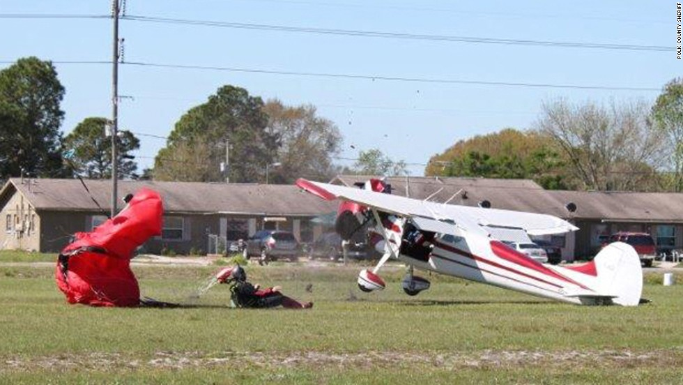 The skydiver sits up after crashing to the ground.
