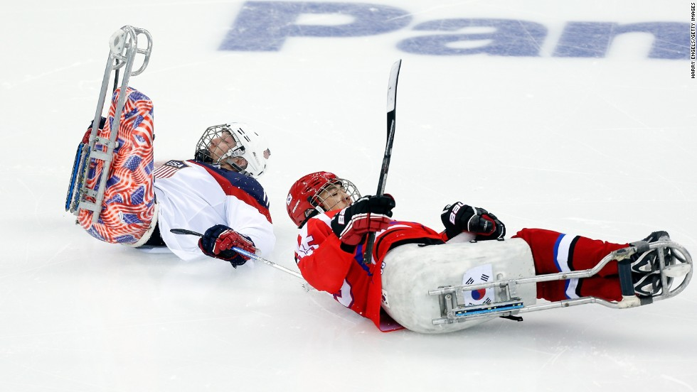 Tyler Carron of the United States, left, collides with Jong Ho-jang of South Korea during a ice sledge hockey game on March 9.