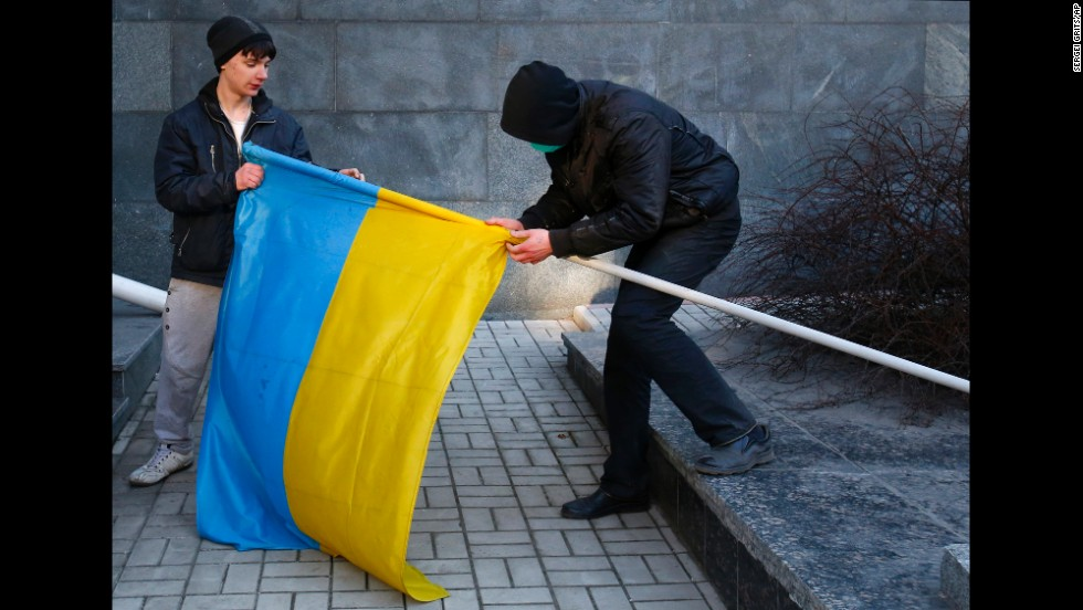 Pro-Russia protesters remove a Ukrainian flag from a flagpole taken from a government building in Donetsk on March 9.