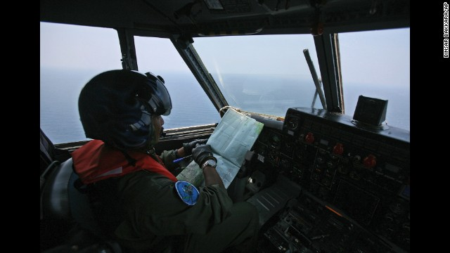 An Indonesian Navy pilot checks his map during a search operation for the missing Malaysian Airlines jet over the waters bordering Indonesia, Malaysia and Thailand near the Malacca straits on Monday, March 10.