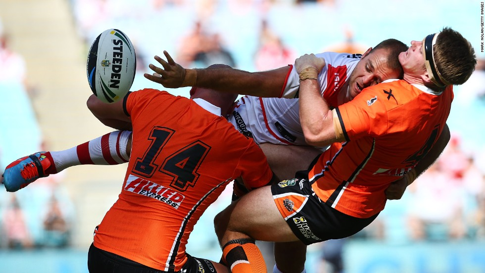 Jason Nightingale of the St. George Illawarra Dragons offloads the ball as he is smashed by two members of the Wests Tigers during a rugby league match Sunday, March 9, at the ANZ Stadium in Sydney.