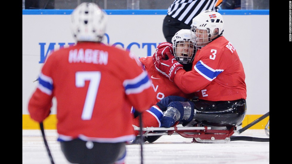 Audun Bakke of Norway, center, celebrates with teammates after scoring Norway's second goal March 11 during their sledge hockey game against Sweden.