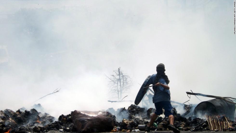 Un manifestante arroja rocas desde una barricada en San Cristóbal el 11 de marzo.