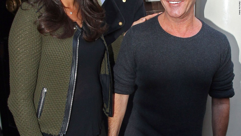 "New parents Simon Cowell and Lauren Silverman beam at a press conference for ""The X Factor"" in London on March 11."