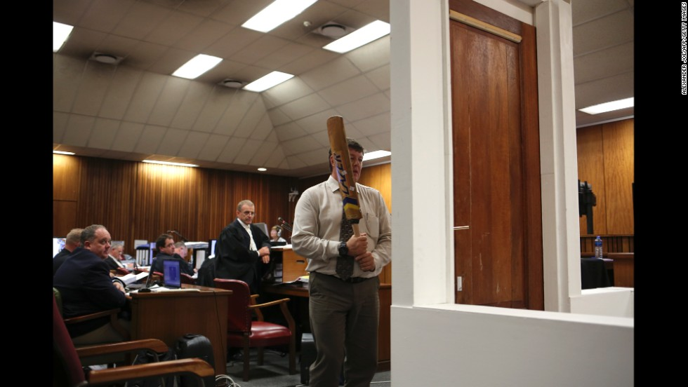 A police officer takes part in a court reconstruction March 12. A police forensic expert said Pistorius was on the stumps of his amputated legs when he knocked down a locked toilet door with a cricket bat to reach his shot girlfriend. That counters the track star's assertion he was wearing his prosthetic legs at the time. Defense attorney Barry Roux countered by suggesting that even with his prosthetic legs on, Pistorius would not be swinging a bat at the same height as an able-bodied person.
