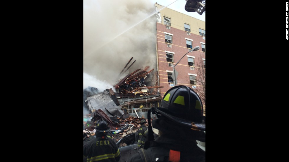 Firefighters examine the damage to one building after the explosion.