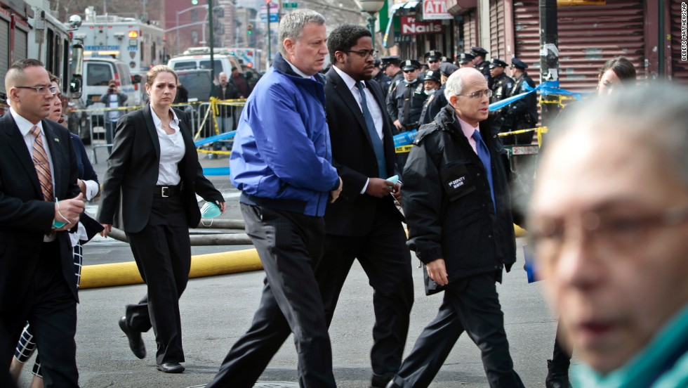 De Blasio, in the blue jacket, arrives at the site of the explosion.