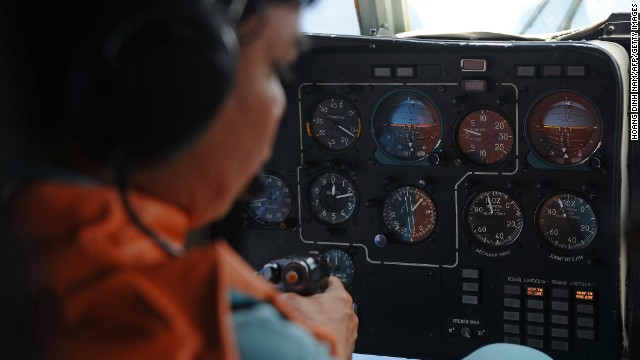 This  picture taken aboard a Vietnamese Air Force Russian-made MI-171 helicopter shows a crew member in the cockpit during a search flight some 200 km over the southern Vietnamese waters off Vietnam's island Phu Quoc on March 11, 2014 as part of continued efforts aimed at finding traces of the missing Malaysia Airlines MH370. Malaysian police said on March 11 one of two suspect passengers who boarded a missing passenger jet was an Iranian illegal immigrant, as relatives of some of the 239 people on board said they were losing hope for a miracle.     AFP PHOTO / HOANG DINH NAM        (Photo credit should read HOANG DINH NAM/AFP/Getty Images)