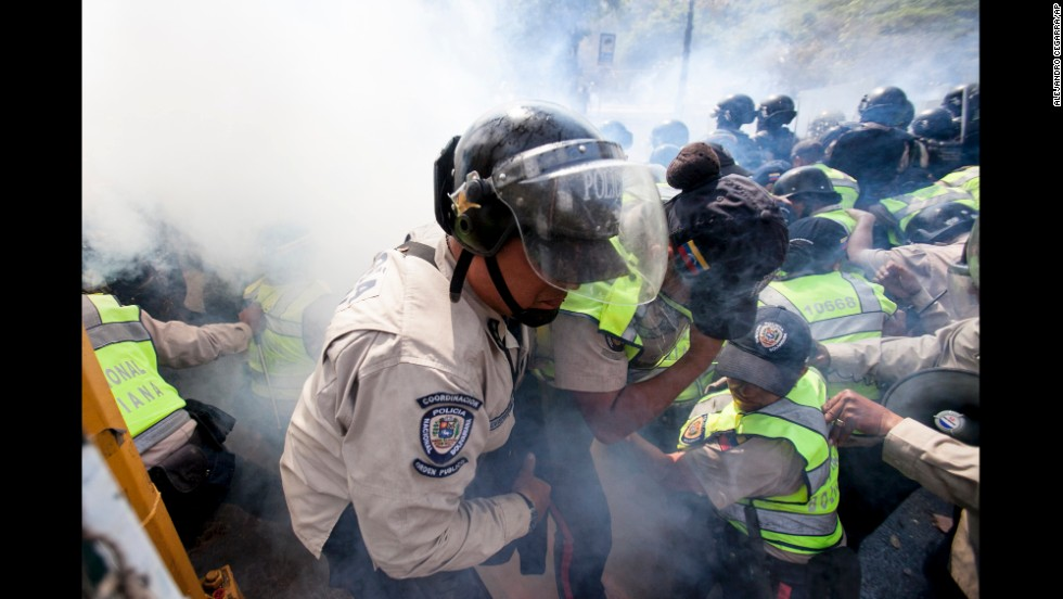 A police officer is removed from the front line of clashes after being overwhelmed by tear gas in Caracas.