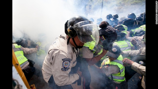 A Bolivarian National Police officer is removed from the front line of clashes in Caracas after being overwhelmed by tear gas.