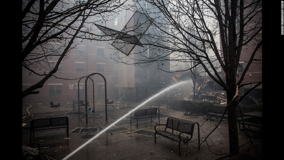 Water is sprayed on smoldering debris close to the scene of the building collapse.