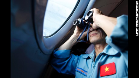 A Vietnamese military official looks out a window, off Vietnam's sea, on Thursday, March 13, inside an aircraft during search operations for the missing Malaysian Airlines jet.