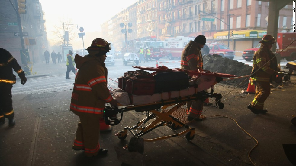 Smoke fills 116th Street as a stretcher is wheeled toward the site of the explosion on March 13.