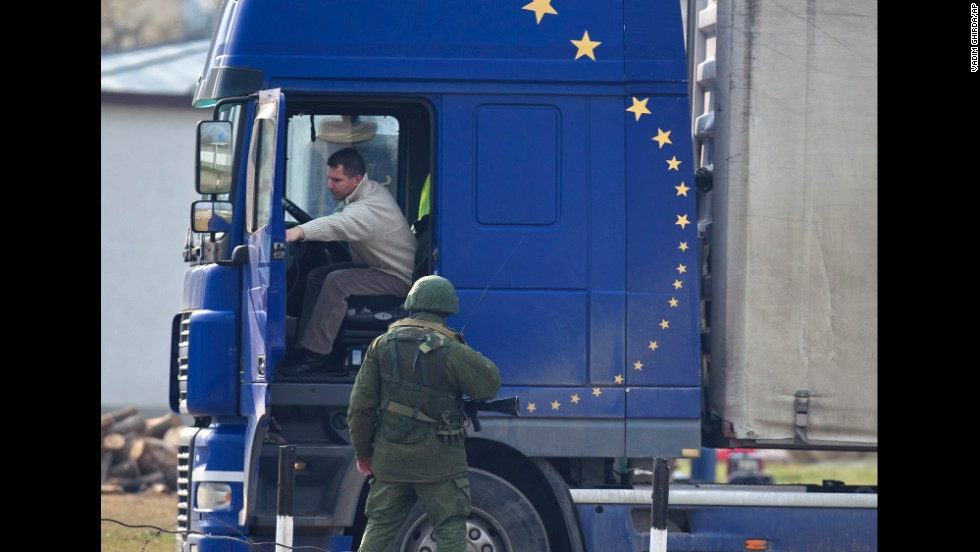 A pro-Russian soldier speaks to a truck driver outside the Ukrainian infantry base in Perevalne on Wednesday, March 12.