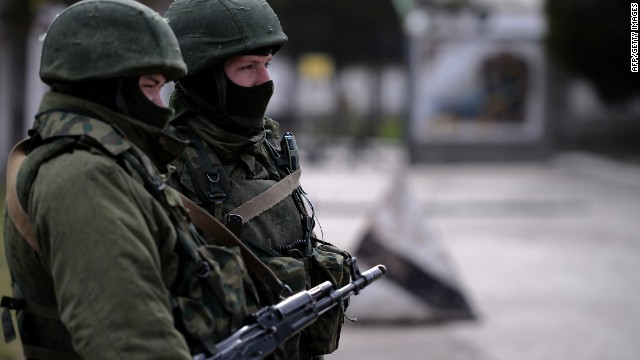 Armed men, believed to be Russian servicemen, stand guard outside an Ukrainian military base in Perevalnoye on March 13, 2014.