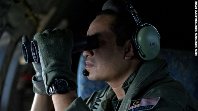 Caption: A crew member uses binoculars onboard a Malaysian Air Force CN235 aircraft during a search and rescue (SAR) operation to find the missing Malaysia Airlines flight MH370 plane over the Strait of Malacca on March 14, 2014. Malaysia confirmed on March 14 that the search for a missing Malaysia Airlines plane had been expanded into the Indian Ocean, but declined to comment on US reports that the jet had flown for hours after going missing. AFP PHOTO / MOHD RASFANMOHD RASFAN/AFP/Getty Images