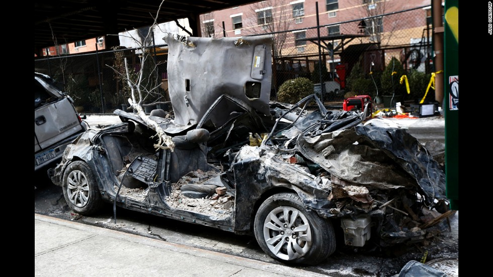 A vehicle crushed by debris from the building explosion is seen on the street.
