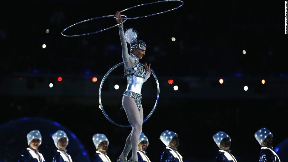 An acrobat balances on a ball as Cossack dancers perform.