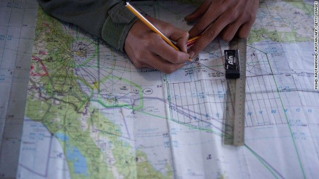 Caption: Royal Malaysian Air Force Navigator captain, Izam Fareq Hassan marks locations on a map onboard a Malaysian Air Force CN235 aircraft during a search and rescue (SAR) operation to find the missing Malaysia Airlines flight MH370 plane over the Strait of Malacca on March 14, 2014. Malaysia confirmed on March 14 that the search for a missing Malaysia Airlines plane had been expanded into the Indian Ocean, but declined to comment on US reports that the jet had flown for hours after going missing. AFP PHOTO / MOHD RASFANMOHD RASFAN/AFP/Getty Images