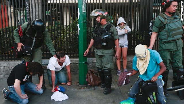Anti-government demonstrators kneel as they are arrested by Bolivarian National Guards during clashes in Caracas, Venezuela, on Sunday, March 16.