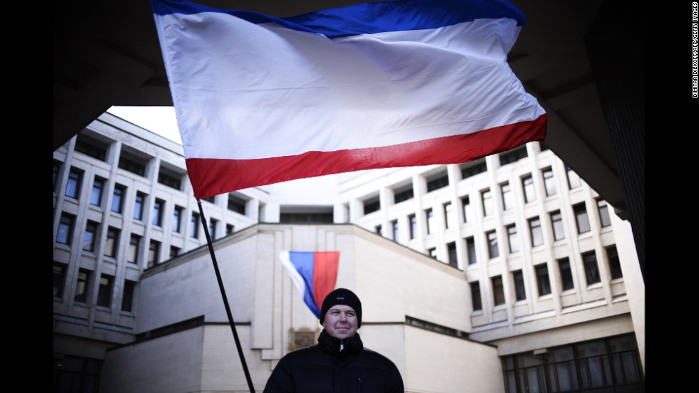 A man holds a Crimean flag as he stands in front of the Crimean parliament building in Simferopol on March 17.