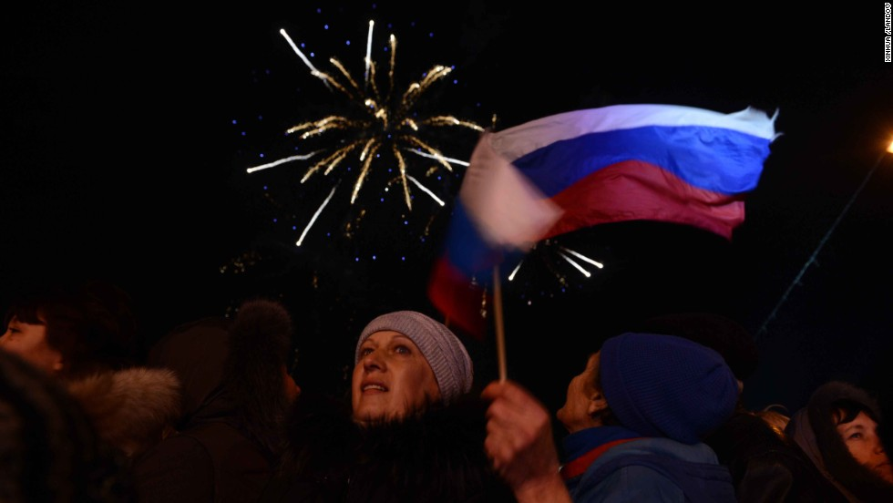 Crimeans holding Russian flags celebrate in front of the parliament building in Simferopol on Sunday, March 16.