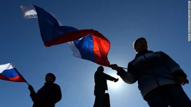 People wave Russian flags in Simferopol's Lenin Square on March 17, 2014.
