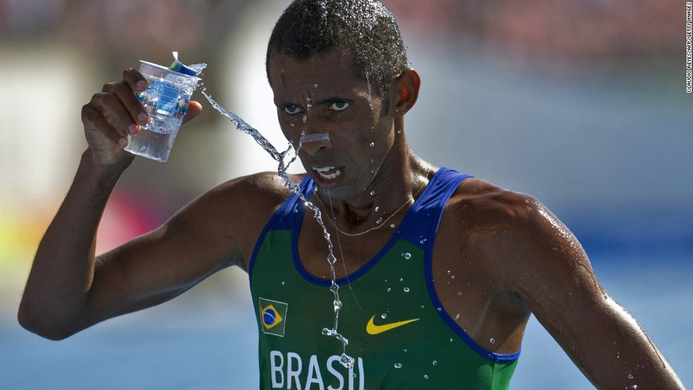 Giovani dos Santos refreshes himself Thursday, March 13, after crossing the finish line in the 10,000-meter race at the South American Games in Santiago, Chile.