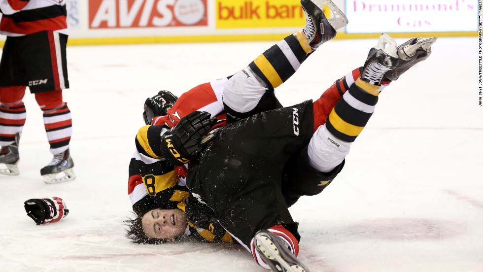 Mack Lemmon of the Kingston Frontenacs falls to the ice after being tackled by Troy Henley of the Ottawa 67's during a fight in their Ontario Hockey League game Tuesday, March 11, in Ottawa.