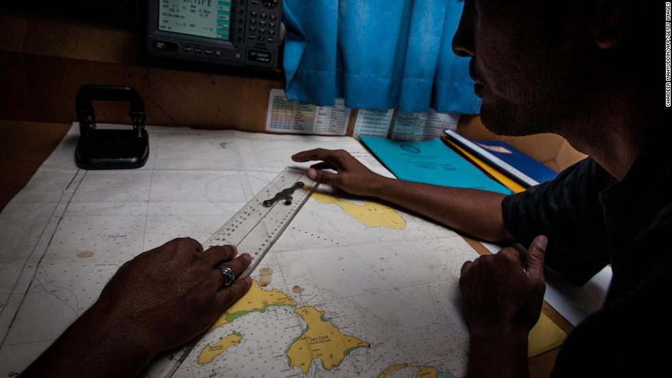 Personal del equipo de búsqueda y rescate de Indonesia revisa un mapa durante las operaciones en el mar de Andamán al norte de la isla de Sumatra.