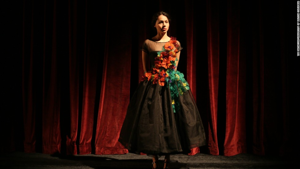 "Mercedes de la Zerda,<strong> </strong>a University of British Columbia acting student,<strong> </strong>models a black organza cap sleeve dress with a sheer top and diagonal multicolor organza trim. With this dress, Firkins says she hoped to express that cancer patients and survivors may want to hide parts of their body and showcase others. ""You can see through one layer into another. You can show your skin but hide it in another way,"" she says."