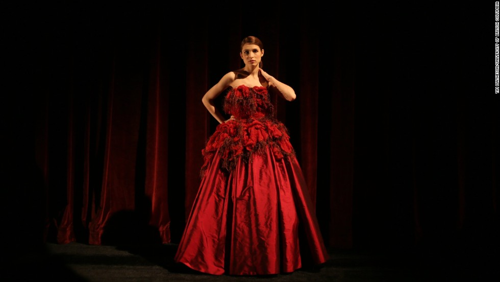 """Chelsi Walsh, a University of British Columbia opera student, models a full-length strapless red silk taffeta dress inspired by the red-stained astrocytes. With this collection, Firkins says she wanted to look at cancer with a sense of optimism and celebration. """"The women I know that have been through cancer are some of the strongest, most inspiring women I know,"""" she says. """"They celebrate life, so I wanted to create something that reflects what they've come through with."""""""