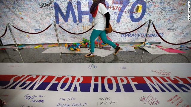 A woman walks past a banner filled with signatures and well-wishes for all involved with the missing Malaysia Airlines jetliner MH370 at the Kuala Lumpur International Airport, Sunday, March 16, 2014 in Sepang, Malaysia. Malaysian authorities Sunday were investigating the pilots of the missing jetliner after it was established that whoever flew off with the Boeing 777 had intimate knowledge of the cockpit and knew how to avoid detection when navigating around Asia. (AP Photo/Wong Maye-E)