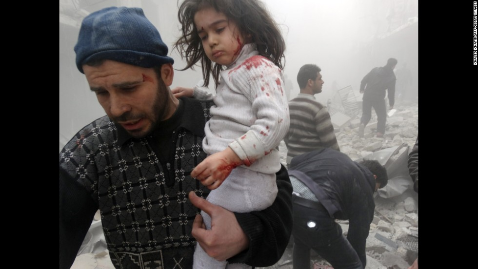 A man carries a child who was found in the rubble of an Aleppo building after it was reportedly bombed by government forces on Monday, March 18.